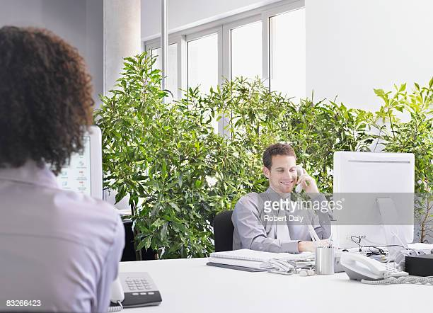Businessman at desk surrounded by plants