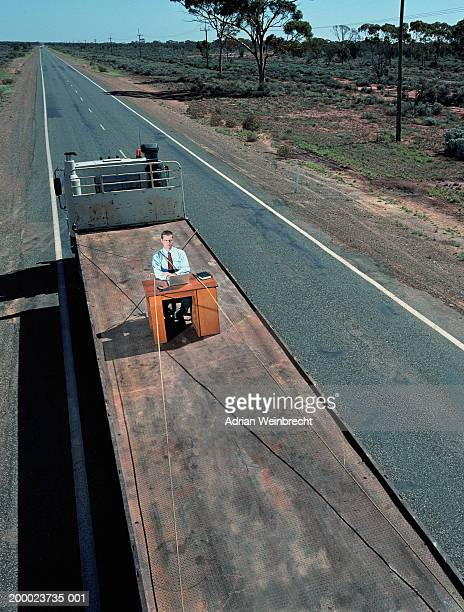 Businessman at desk tied to back of truck, elevated view