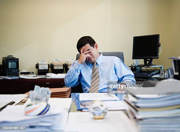 Businessman at desk with hand on head