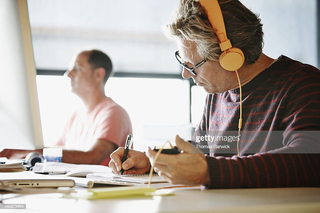 Businessman at desk writing in notepad : Stock Photo