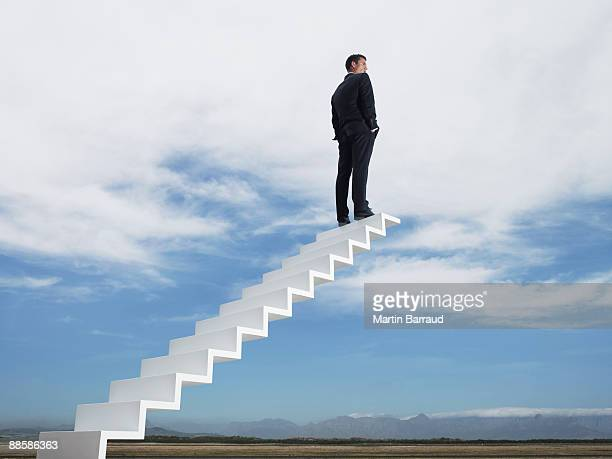 Businessman at end of stairway leading to the sky