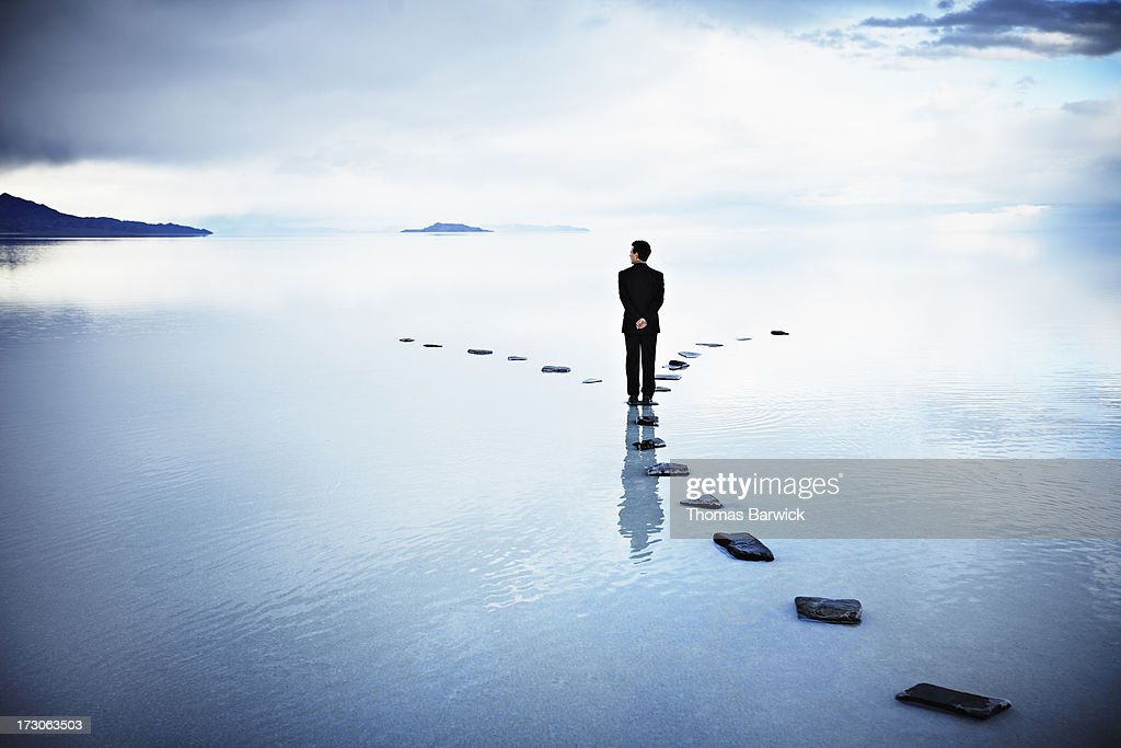 Businessman at fork of stone pathway in water : Photo