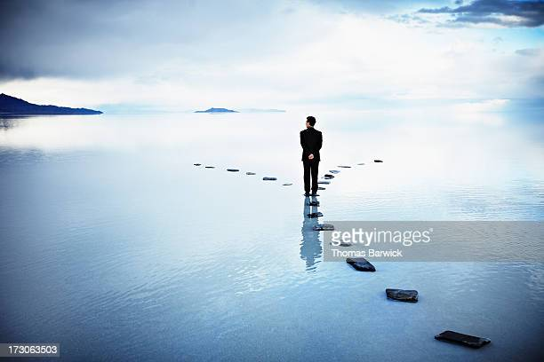 businessman at fork of stone pathway in water - beslissingen stockfoto's en -beelden