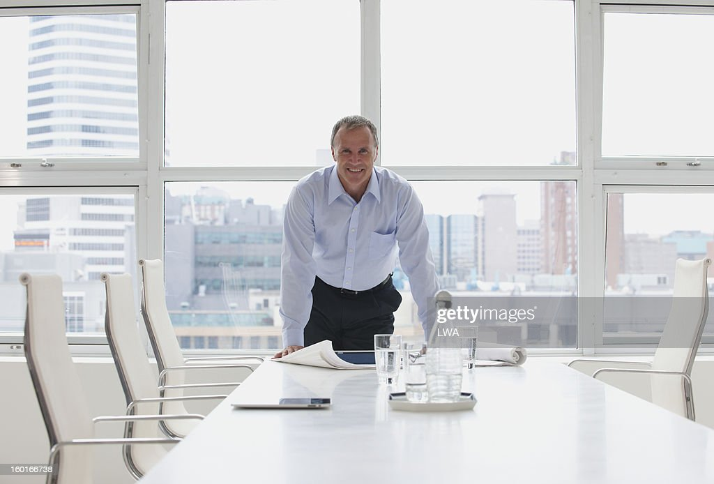 Businessman at head of boardroom table : Stock Photo