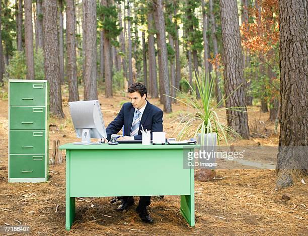 Um empresário na sua secretária na floresta