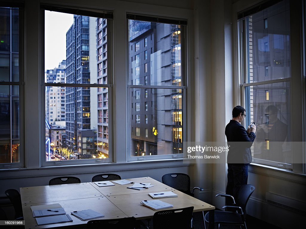 Businessman at office widow working on smart phone : Bildbanksbilder