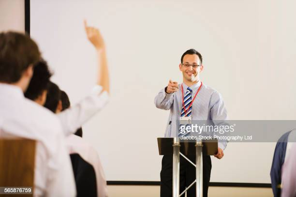 Businessman at podium taking question from audience