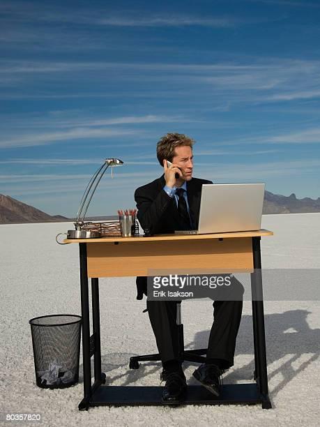Businessman at salt flats talking on cell phone, Salt Flats, Utah, United States
