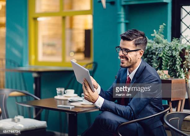 Businessman at sidewalk cafe using tablet pc