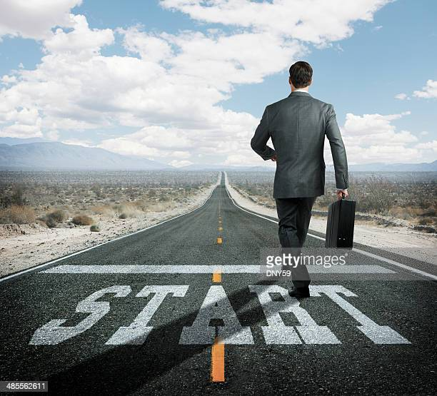 Businessman at starting line begins journey down remote highway
