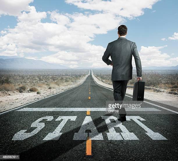 Uomo d'affari presso la linea di partenza Inizia il viaggio verso l'autostrada remoto