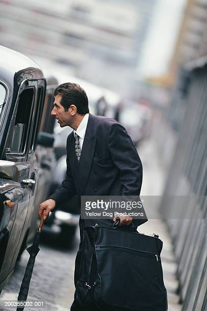 Businessman at taxi queue, side view