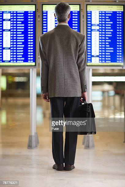 Businessman at the Airport Looking at Departure Monitor
