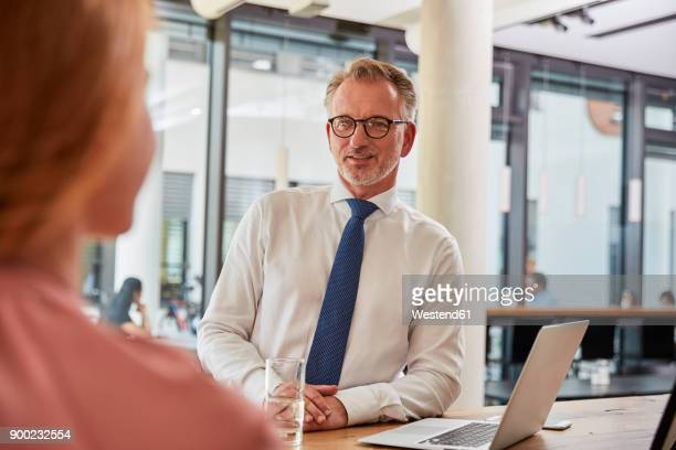 Businessman at the airport talking to young woman