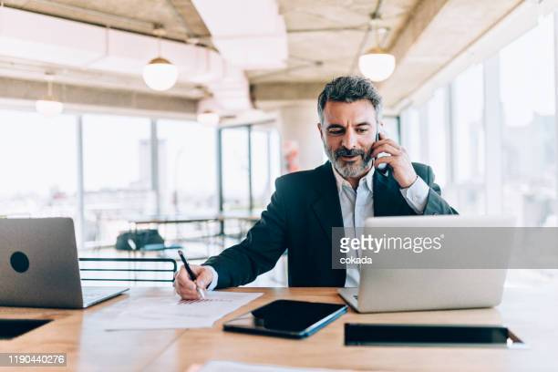 empresario de la oficina hablando por teléfono celular - negocios finanzas e industria fotografías e imágenes de stock