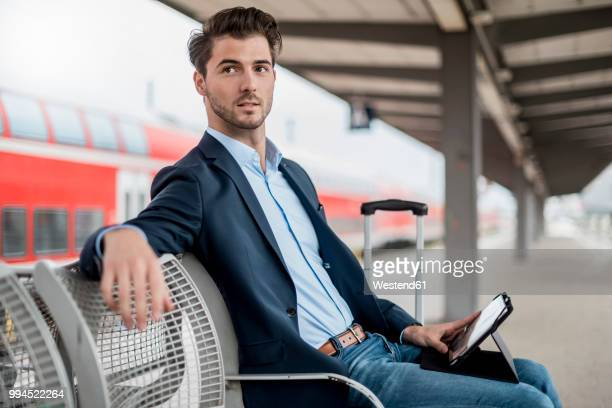 businessman at the station using tablet - bahnreisender stock-fotos und bilder