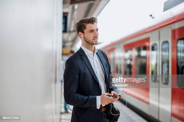 businessman at the station with earbuds and cell phone - bahnreisender stock-fotos und bilder