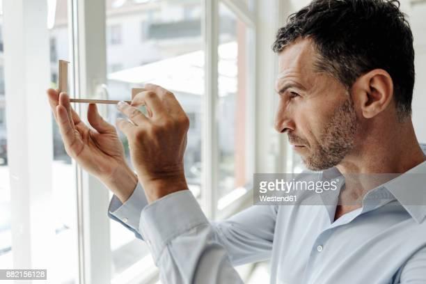 businessman at the window looking at architectural model - genauigkeit stock-fotos und bilder