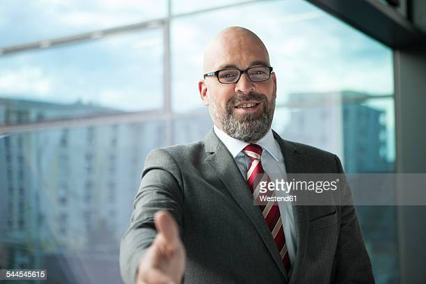 Businessman at the window reaching out his hand