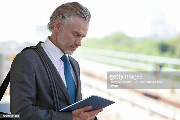 Businessman at train station using digital tablet