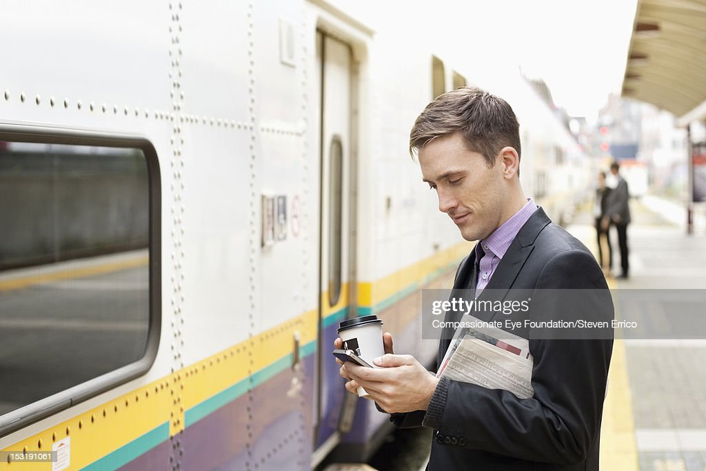Businessman at train station using mobile phone : Stock Photo