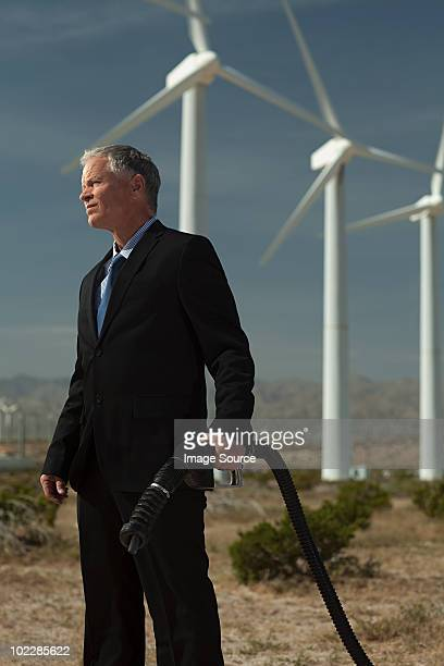 Businessman at wind farm with gas pump