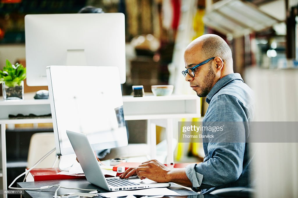 Businessman at workstation in startup office : Stock Photo