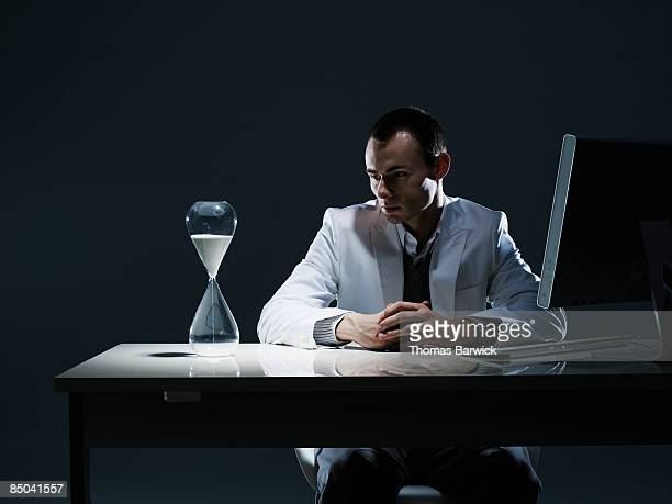 businessman at workstation watching hourglass - prazo - fotografias e filmes do acervo