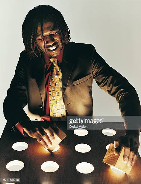 Businessman attempting to insert Wooden Cubes into Circular Holes