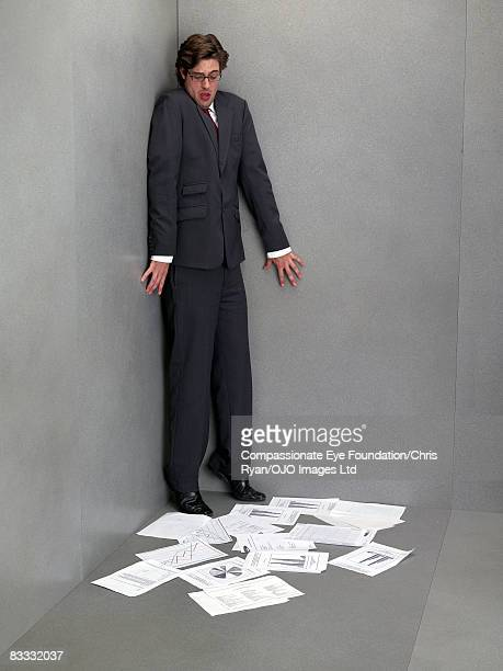 Businessman backed into corner, charts on floor