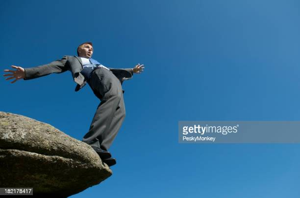 Businessman Balances at Edge of Cliff