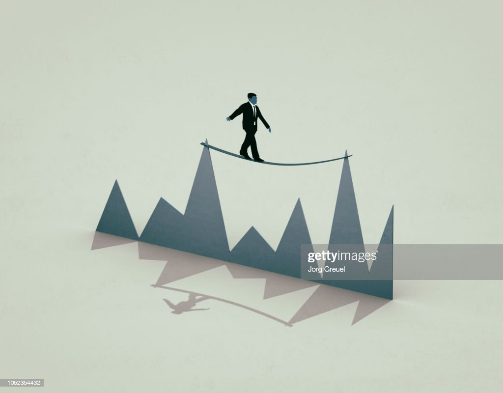 Businessman balancing between two peaks of a graph : Stock Photo
