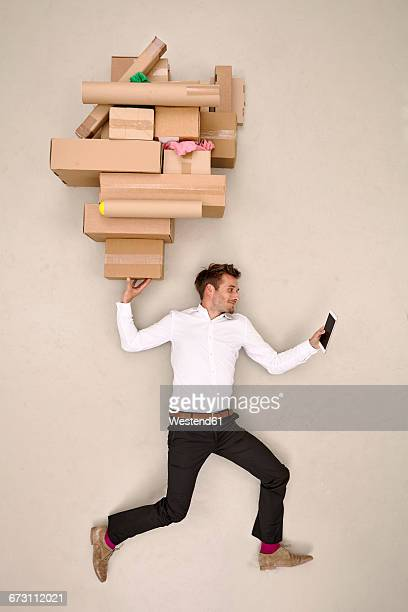businessman balancing cardboard boxes and looking on smartphone - commodité photos et images de collection