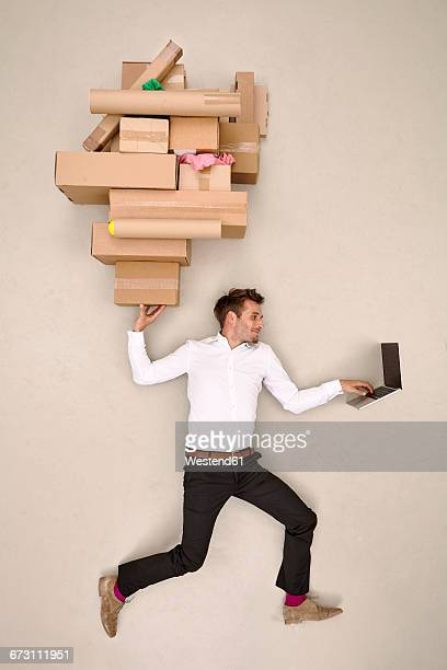 Businessman balancing cardboard boxes and working on laptop