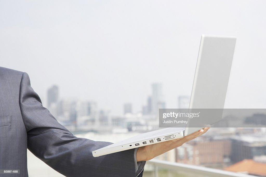 Businessman balancing laptop on hand, close up : Stock-Foto