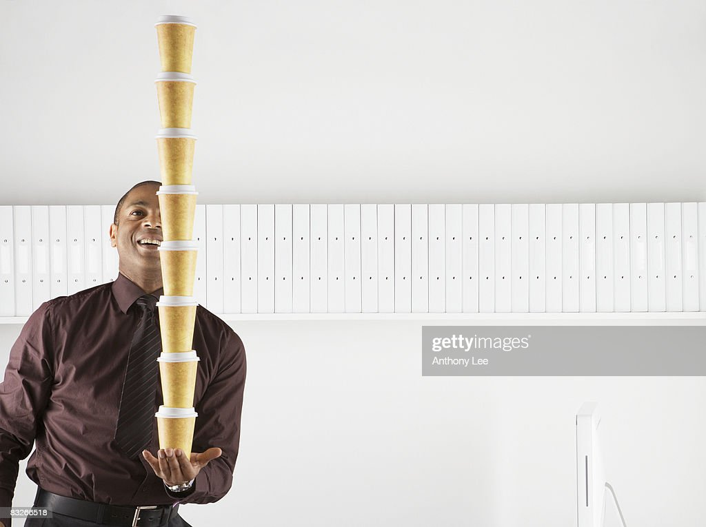 Businessman balancing large stack of paper coffee cups : Stock Photo