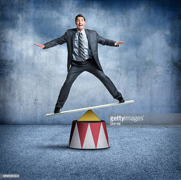Businessman Balancing On A Circus Pedestal