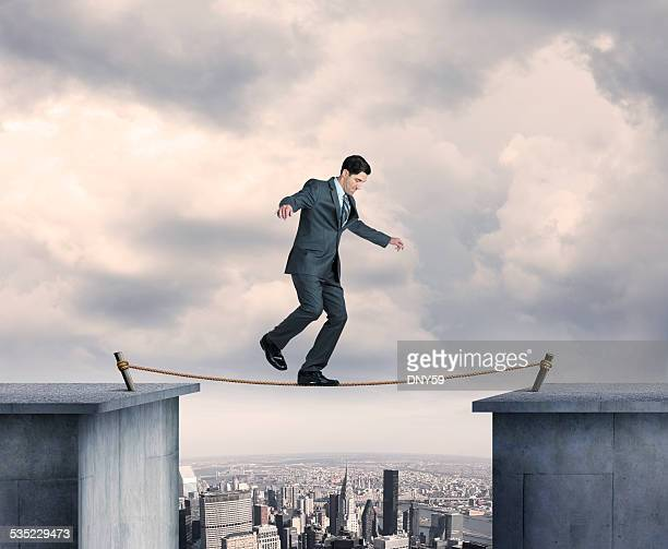 Businessman Balancing On A Tightrope Above Big City