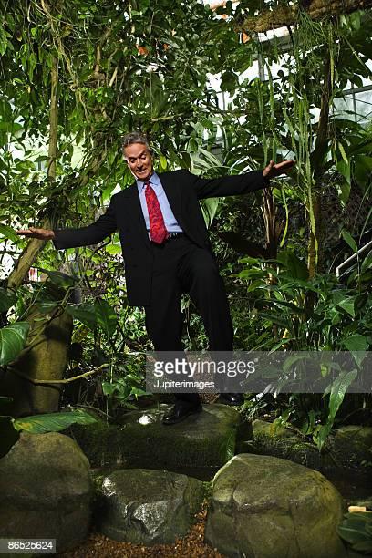 Businessman balancing on rock
