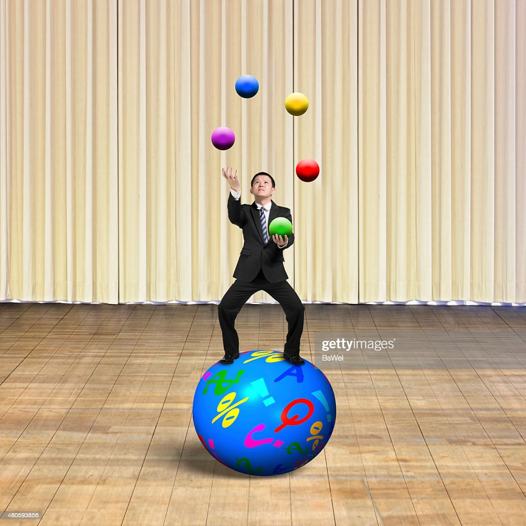 Businessman balancing on sphere juggling with balls : Stock Photo