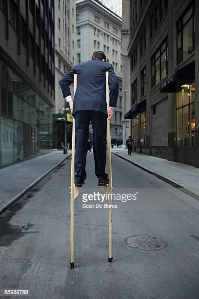 Businessman balancing on stilts