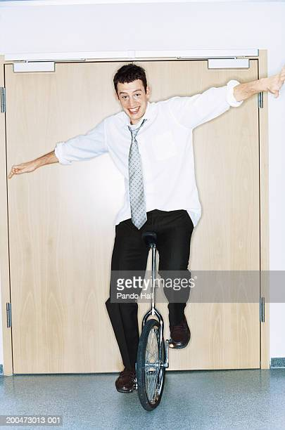 Businessman balancing on unicycle in office, smiling, portrait