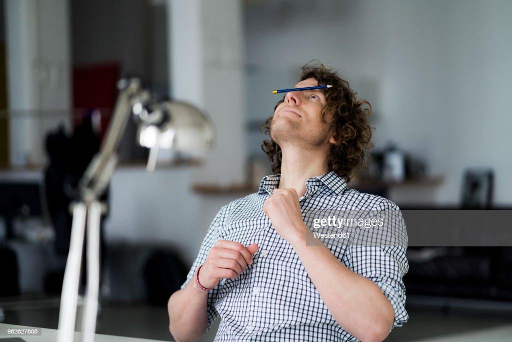 Businessman balancing pencil on his face : Stock Photo