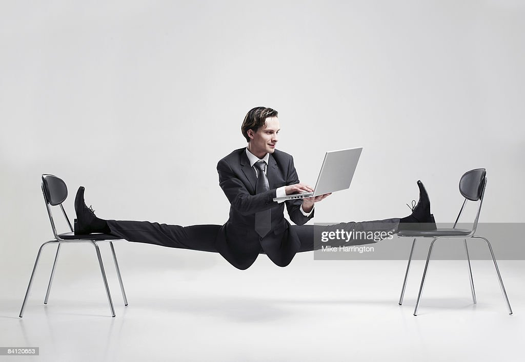 Businessman balancing to two chairs holding laptop : Stock Photo
