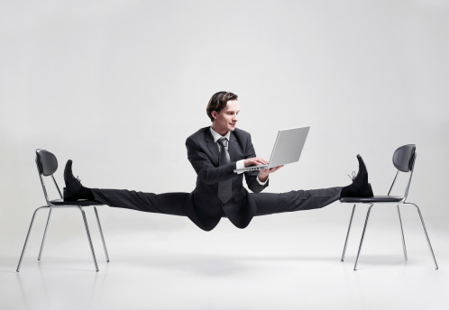 Businessman balancing to two chairs holding laptop - gettyimageskorea