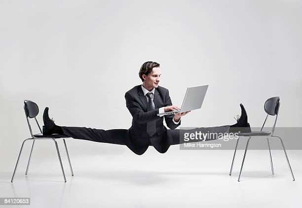 Businessman balancing to two chairs holding laptop