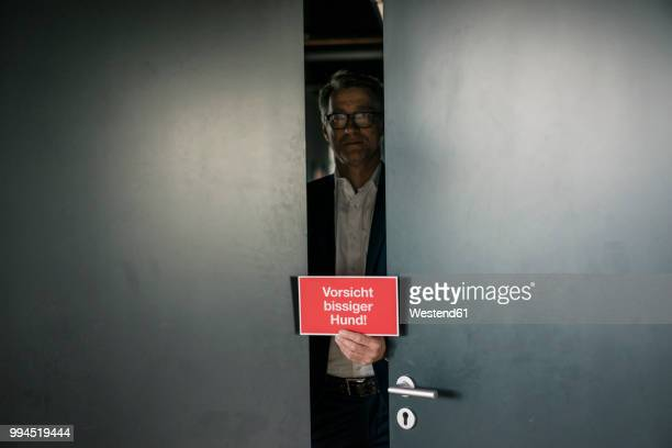 businessman behind door holding sign - ajar stock pictures, royalty-free photos & images
