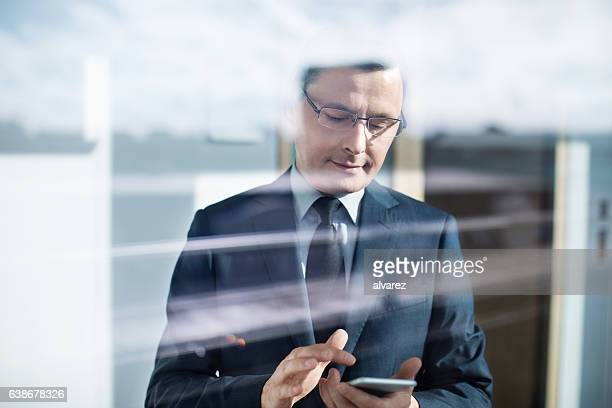 Businessman behind glass window using mobile phone