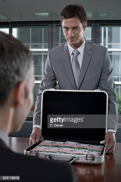 Businessman Being Bribed with Suitcase Full of Euros