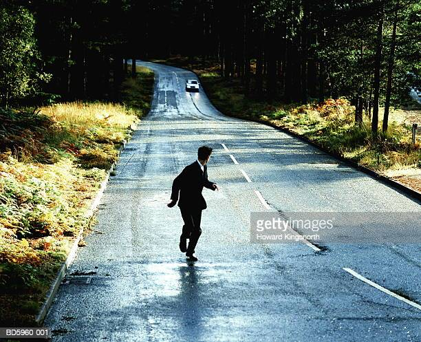 Businessman being chased by car